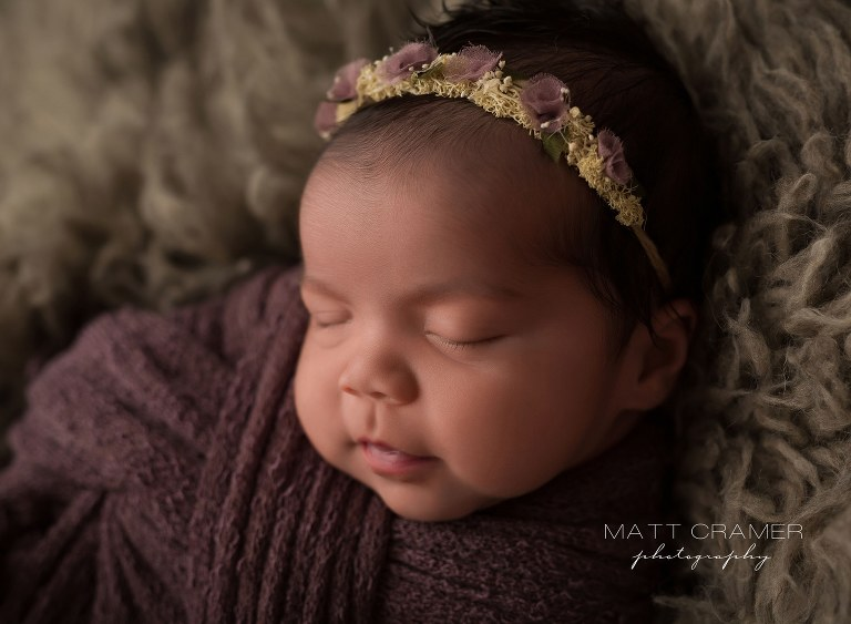 baby girl sleeping in purple swaddle with boho style headband Newborn Photography in Los Angeles
