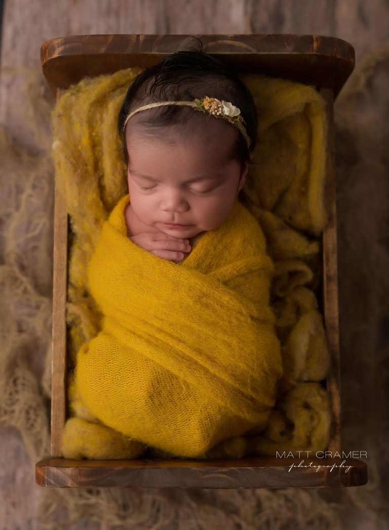 Newborn baby girl sleeping in baby bed while being photographed at her Newborn Photography in Los Angeles