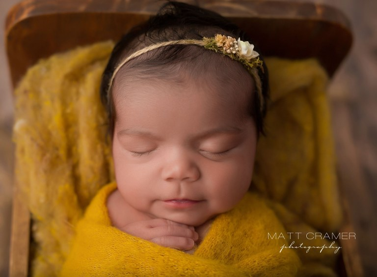 Newborn baby girl swaddled and wrapped in yellow fabric sleeping in wood baby bed photography prop during her Newborn Photography session in Los Angeles