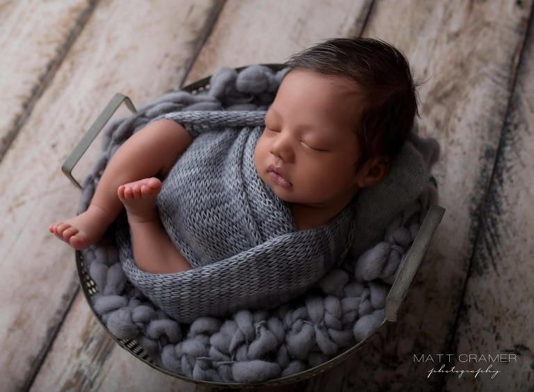newborn baby boy in swaddle wrap during a photo shoot