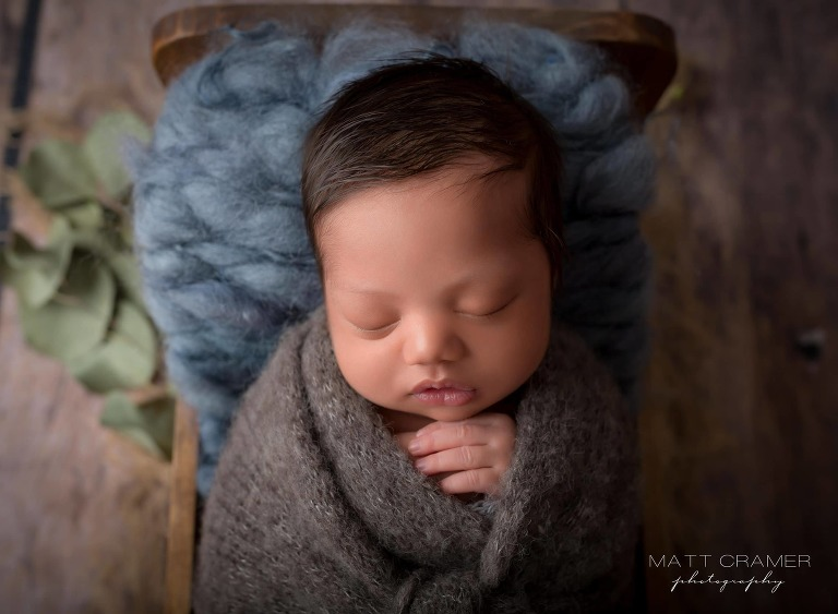 new born baby boy posed in wood baby bed prop