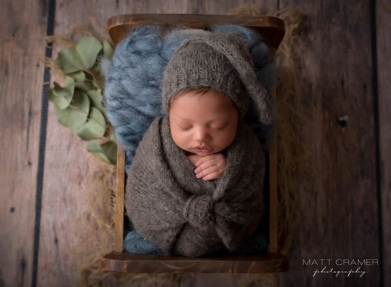 infant baby boy wearing sleepy hat during newborn photography session.