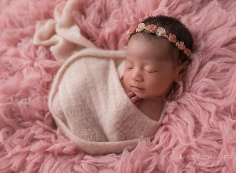 newborn baby in a light pink swaddle, laying on pink textured background during a newborn photography session
