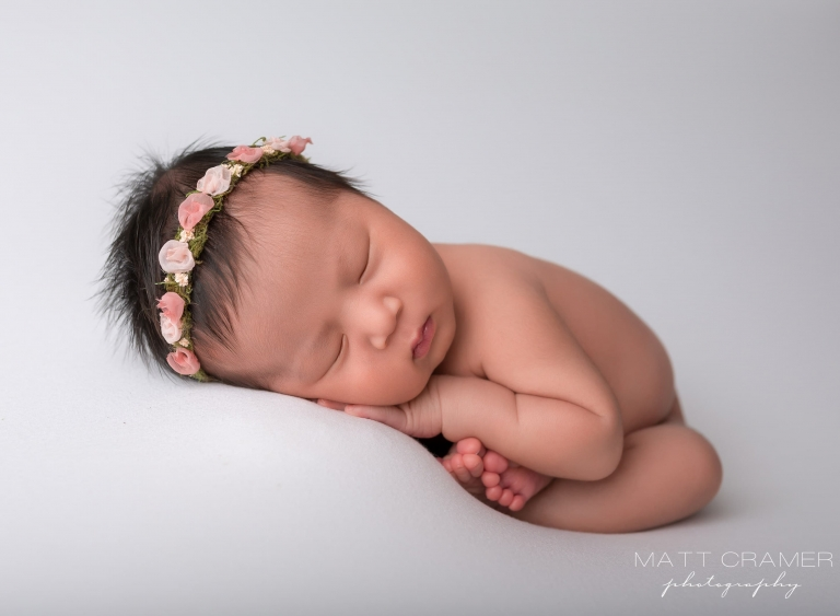 newborn baby posed on solid white fabric during a newborn photography session